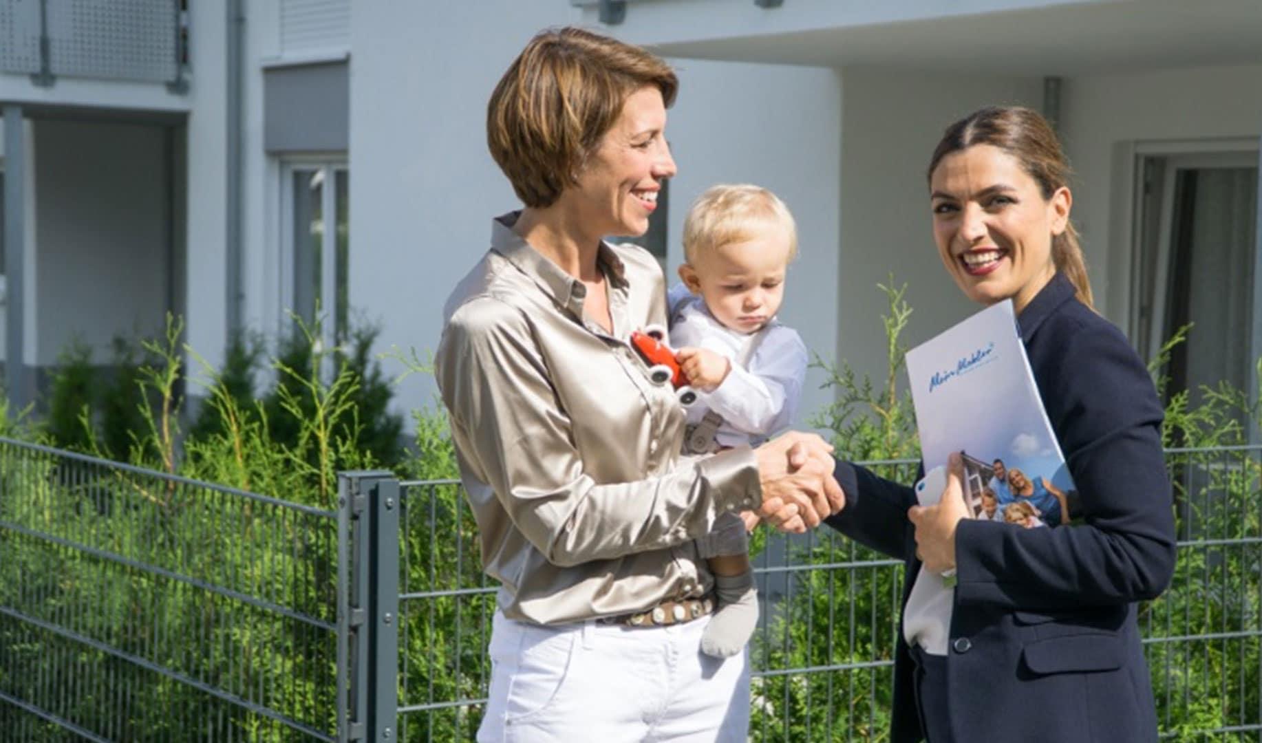 Mutter mit Kind im Beratungsgespräch mit Makler